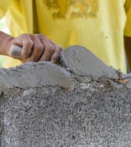 Concrete worker spreading cement and smoothing a concrete surface